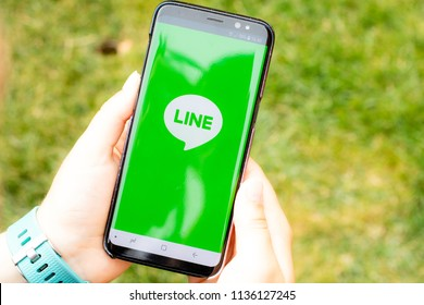 Lincoln, United Kingdom - 07/16/2018: The load screen for the Line messaging app made by Naver, being held by a young girl
