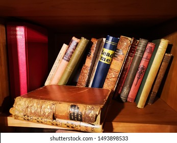 LINCOLN, UNITED KINGDOM 25th August, 2019: A book shelf with dusty old hardback books and novels in a row to borrow and read