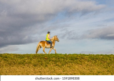 Lincolnshire, England UK. November 9 2017. Lone horse rider with cloudy sky. With no other features.