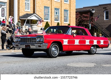 """LINCOLNTON, NC, USA-11 NOV 2019: Red 1964 Chevrolet Impala driven in a veterans' parade, with printed signs saying: """"Army"""", """"Air Force"""", """"Coast Guard"""", """"Marines"""", and """"Navy""""."""