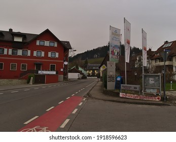Lindau, Bavaria, Germany - 02-06-2021: Center of small village Schönau, part of Lindau, with main road, bicycle lane, hotel, advertising flags and residential building on cloudy winter day.