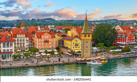 Lindau, Germany. Antique Bavarian town in Bavaria at coastline of Lake Constance (Bodensee). Habour along embankment with traditional houses and tower. Sunset evening landscape.