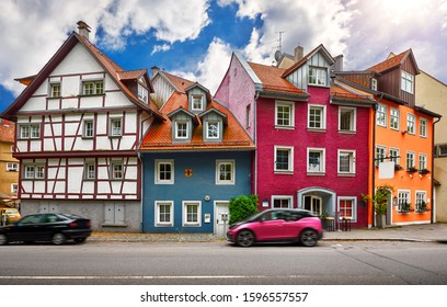 Lindau, old town on Lake Constance (Bodensee), Bavaria, Germany. Motley colorful traditional german bavarian houses along street with cars. Day cityscape with architecture blue sky and clouds.
