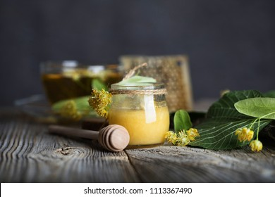 Linden blossoms honey in a glass bottle on a wooden surface. Closeup