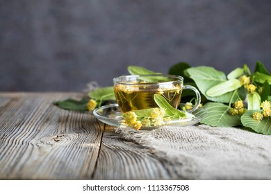 Linden blossoms tea in a glass cup on a wooden surface. Closeup