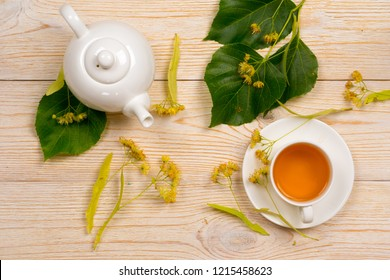 linden herbal tea with raw plant on wooden table