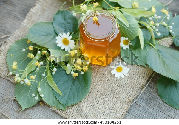 linden honey with linden leaves and flowers on canvas and wooden background
