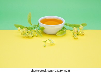 Linden honey in a white ceramic plate on a yellow and lime green background, decorated with the fresh linden blossom; a space for a text. Horizontal.