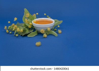 Linden honey in a white ceramic plate with fresh linden blossom.