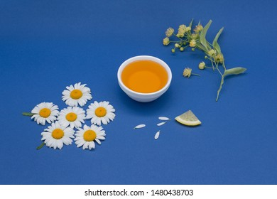 Linden honey in a white ceramic plate with fresh linden blossom, camomile and small piece of lemon on blue background.