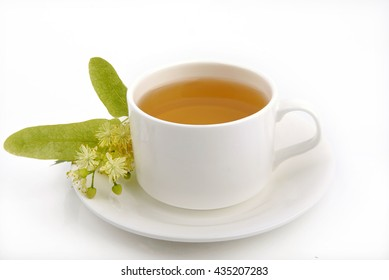 Linden tea in a white cup and saucer and linden flowers on a white background.