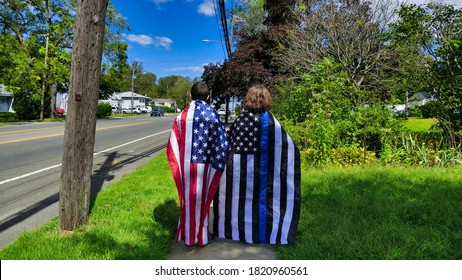 Lindenhurst, New York, September 2020 - Two people standing , with flags on there backs, one American Flag and the other a Thin Blue Line Flag ,during a Blue Lives Matter Parade. High quality photo