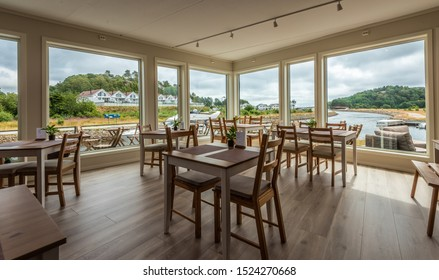 Lindesnes, Norway - July 21 2019: A cabin cruiser passing through the canal viewed from inside of Le Bistro cafe.