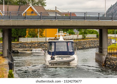 Lindesnes, Norway - July 21 2019: A cabin cruiser barely passing under a bridge over the canal at Spangereid.