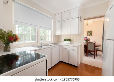 Lindfield, Sydney, Australia - Nov 16 2020: Small kitchen in apartment unit with cork floors and white cabinets, sink and stove.