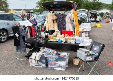 LINDOME, SWEDEN - JUNE 15, 2019: This stand at the car boot sale is selling clothes, CDs and miscellaneous household goods. There's a table, clothing rack and boxes behind the car to display the items