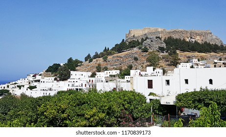 Lindos Castle Rhodes laying behind the white small Lindos houses and trees