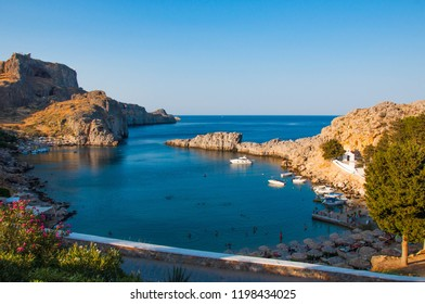 Lindos, Greece - August 11, 2018: Cove with acropolis located on a rock, Lindos city at sunset, Greece