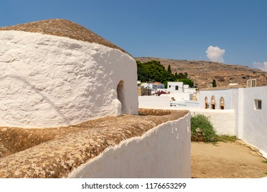Lindos, Greece - August 5, 2018: Architecture of the historical acropolis of Lindos on the Greek island of Rhodes in Greece, with tourists walking around.