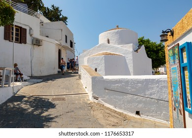Lindos, Greece - August 5, 2018: Street view of the historical acropolis of Lindos on the Greek island of Rhodes in Greece, with tourists walking around.