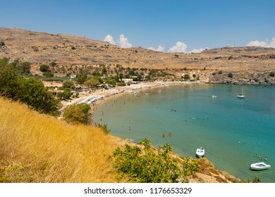 Lindos, Greece - August 5, 2018: Tourists enjoying the beach of Lindos on the island of Rhodes in Greece.