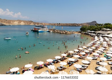 Lindos, Greece - August 5, 2018: Tourists discovering the beach of Lindos on the island of Rhodes in Greece.