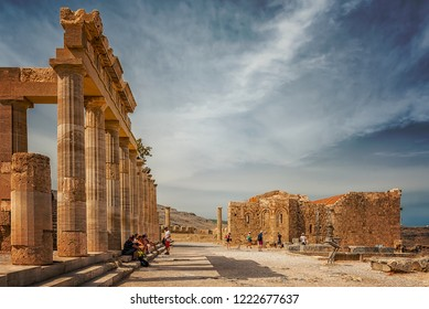 LINDOS, GREECE - OCTOBER 04, 2018: The ruins of this ancient citadel at Lindos sits proudly atop a steep cliff with sea views and can be reached by foot or donkey.