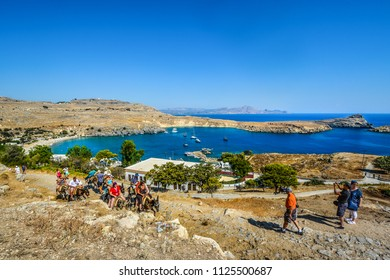 Lindos, Greece - September 16 2017: Tourists ride donkeys up the hill towards the Lindos Acropolis with the Bay of Lindos in view on the island of Rhodes, Greece
