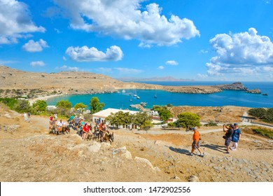 Lindos, Greece - September 16 2018: Tourists ride donkeys up the hill towards the Lindos Acropolis with the Bay of Lindos in view on the island of Rhodes, Greece