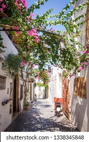 LINDOS, GREECE - SEPTEMBER 8 2018: Beautiful white streets with pink bougainvillea flowers in Lindos, Rhodes, Greece