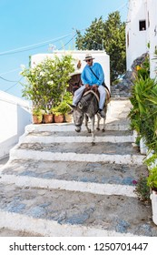 LINDOS, ISLAND OF RHODES, GREECE – AUGUST 17 2017:  Man rides donkey down stairs in village of Lindos