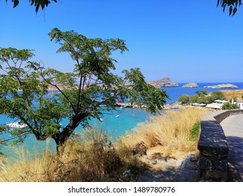Lindos, Island of Rhodes/Greece - circa august 2019: View over dry grass and treetop on Saint Pauls Bay from Acropolis at Lindos