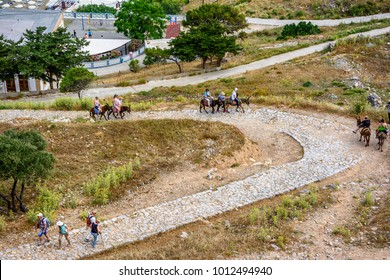LINDOS, Rhodes, GREECE - 8 MAY 2014: Traveling tourists to the acropolis of Lindos on donkeys