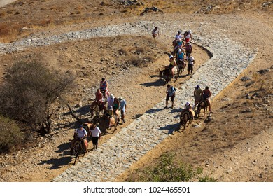 Lindos, Rhodes / Greece - June 23, 2014: Donkeys with tourist in Lindos, Rhodes, Dodecanese Islands, Greece.