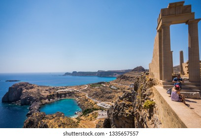 LINDOS, RHODES, GREECE - SEPTEMBER 07 2018: Azure heart shaped sea bay in Lindos, Rhodes, Greece. Beautiful blue St Paul's bay near Acropolis of Lindos