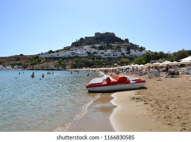 Lindos, Rhodes, Greece - September 22 2014:  White and red pedal boats (pedalo) on the beach of Lindos. Spectacular view from the beach to the all village and the Acropolis of Lindos