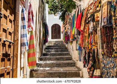 LINDOS, RHODES ISLAND, GREECE - APRIL 30, 2017 ; Colorful scarves in the gift shop. On the way to Acropolis in Lindos.