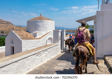 LINDOS, RHODES ISLAND, GREECE - JULY 9, 2015: Tourists riding a donkeys past the chapel of Saint George Pahimahiotis