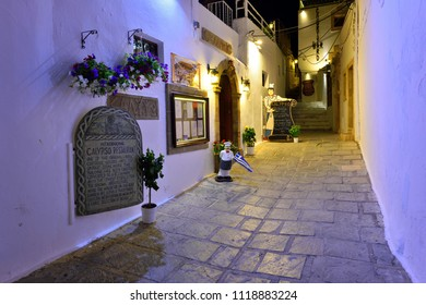 LINDOS, RHODES ISLAND, GREECE - JUNE 03, 2018: Traditional Greek Restaurant in Medieval Lindos Old Town Alley at Night