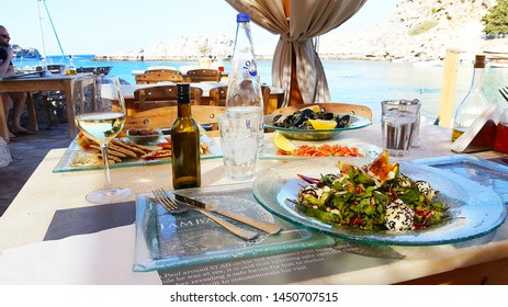 Lindos Village in Rhodes Island Greece - July 2017 Traditional Seafood Dishes on Saint Paul Bay