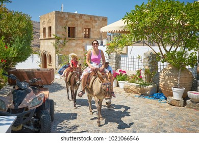 LINDOS/GREECE - August 23, 2017: Woman and her child riding on donkeys in Lindos town