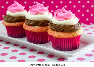 Line up of 3 neapolitan frosted cupcakes on white plate with pink polka dot table and background