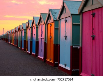 a line of 30 beach huts with a diminishing perspective, the nearer beachhuts are big, lamp post and promenade, brighton seafront