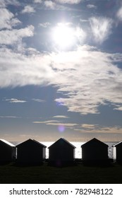 A line of 5 Beach huts silhouetted black by the sun shining directly at the camera through a dramatic blue and white sky, the sea is shimmering behind the beach huts,
