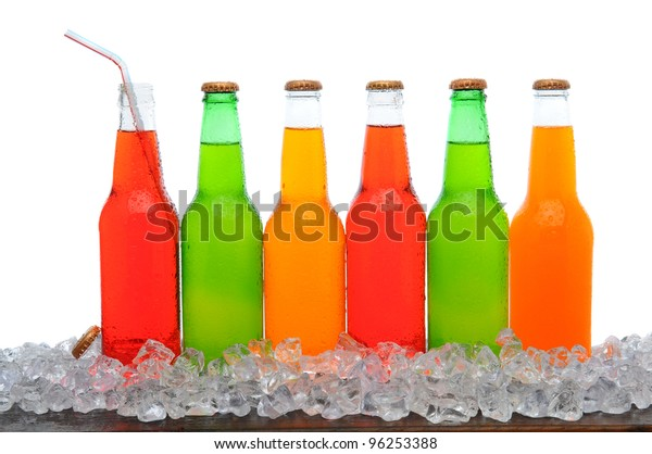A line of assorted soda bottles standing in a field of ice cubes on a wooden table. Horizontal format with a white background.