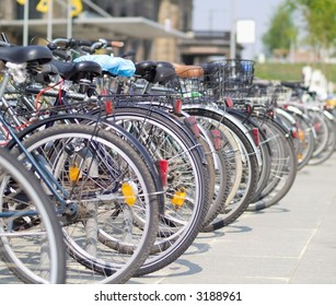 line of bicycles in front of a train station