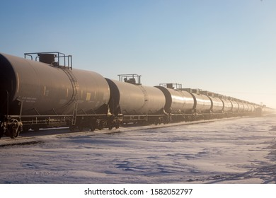 Line of Black Railroad Tank Cars in Winter With Snow and Blue Sky on Prairie