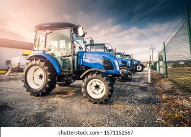 Line of blue tractors prepared for agricultural customers at dealership parking lot. Stock blue tractors prepared to be sold.