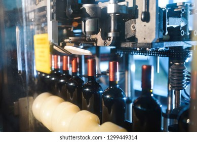 line of bottles with red top at wine factory