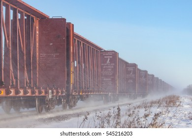Line of brown flatcars blowing snow